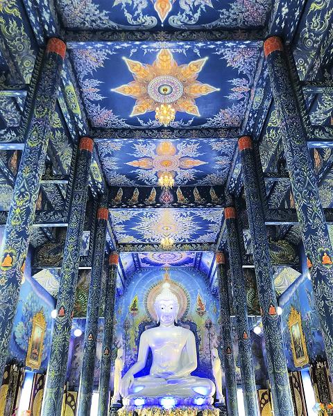 Tượng Phật trắng nổi bật giữa nền xanh của đền