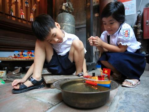 Trẻ em thích thú vì tàu thủy sắt tây có thể nổi trên mặt nước.