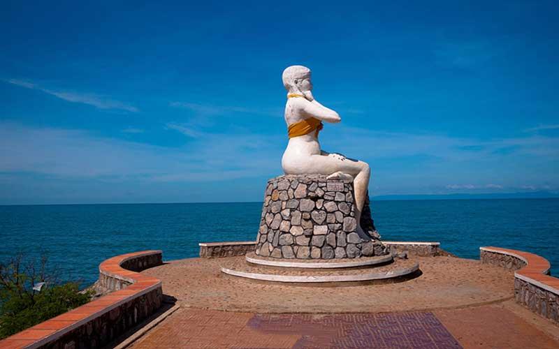 Một pho tượng thiếu nữ to cao dựng tại một mũi đất nhô ra biển