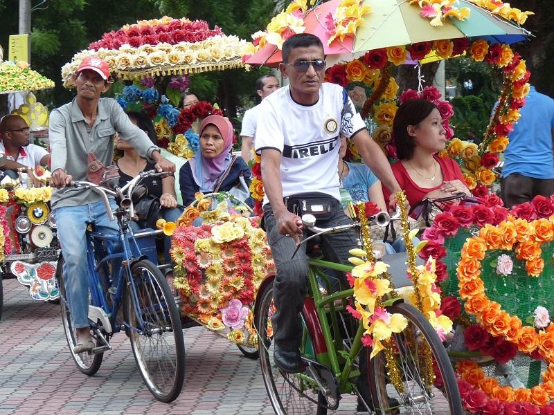 Khách du lịch hào hứng ngồi xe trishaw chạy quanh phố biển Malacca